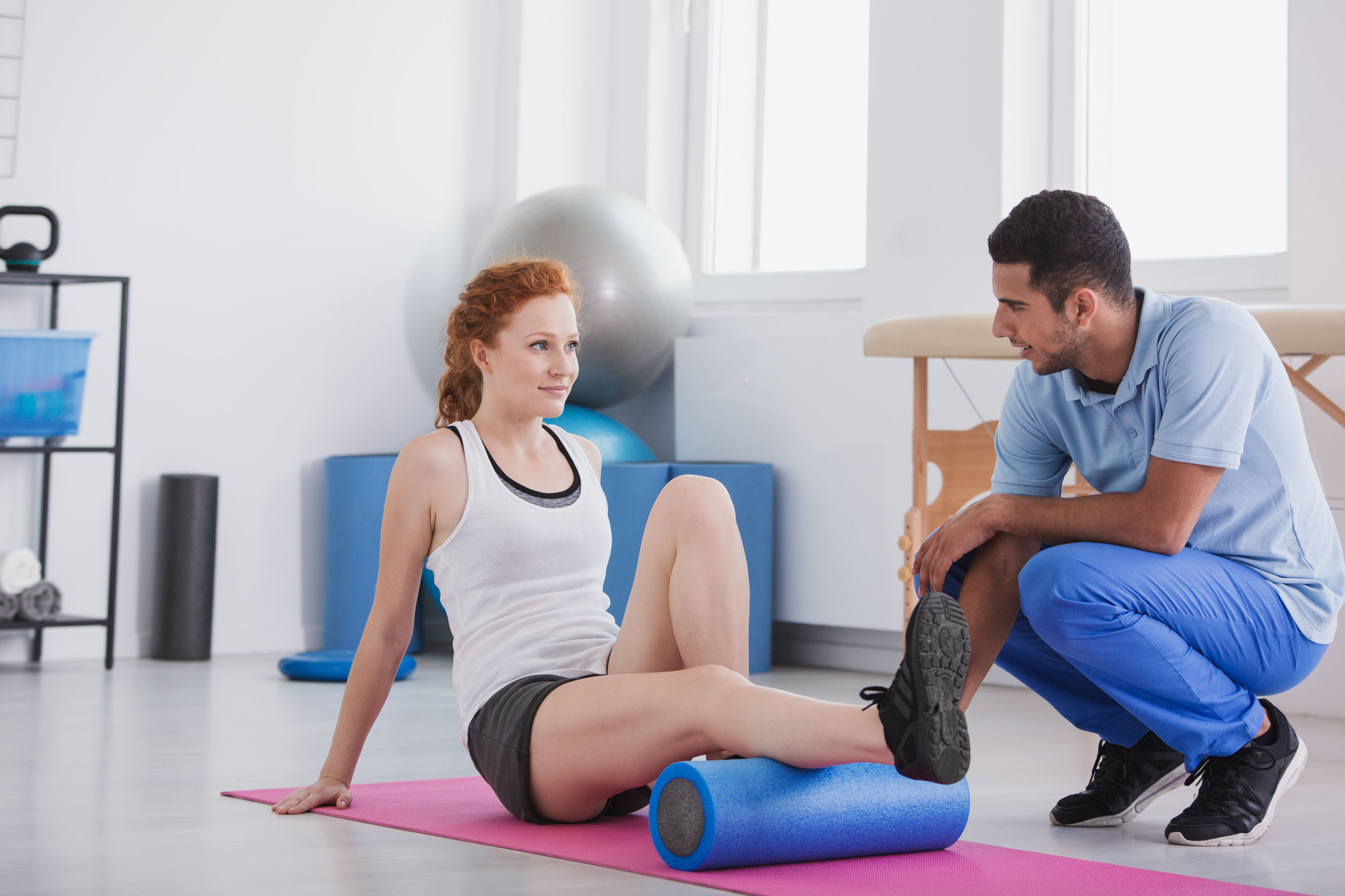 Young woman working out with a foam roller on a mat supported by her trainer