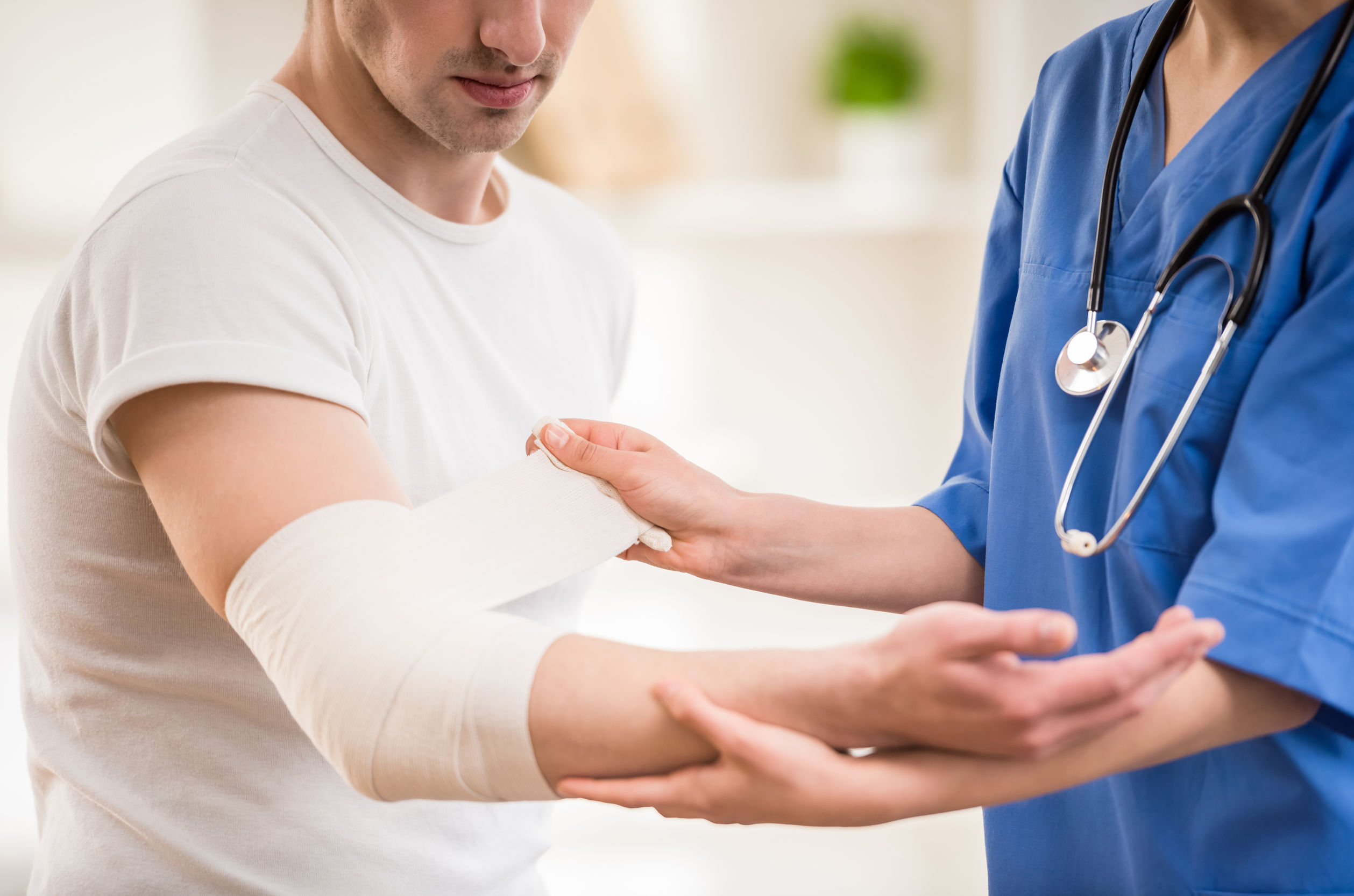 Close-up of female doctor with stethoscope  bandaging hand of male patient.