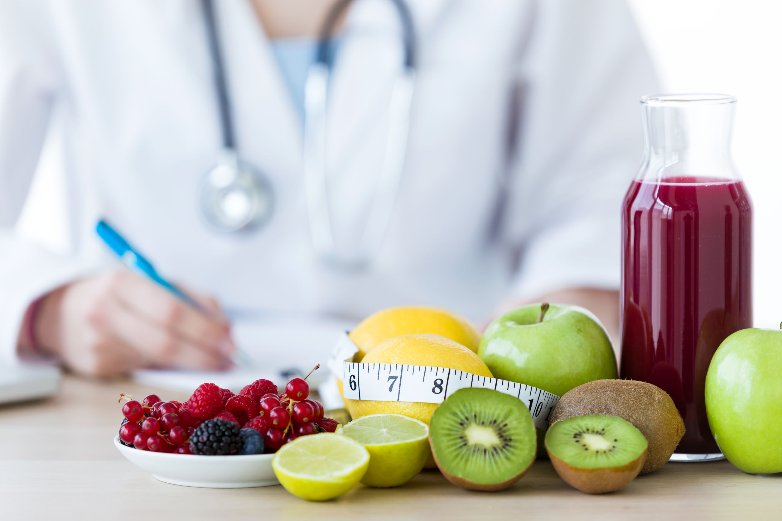 Close-up of some fruits such as apples, kiwis, lemons and berries on nutritionist table.